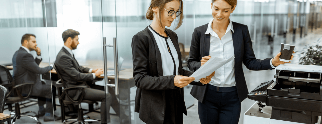 two business woman standing at a copier in an office hallway, copier leasing concept for any company