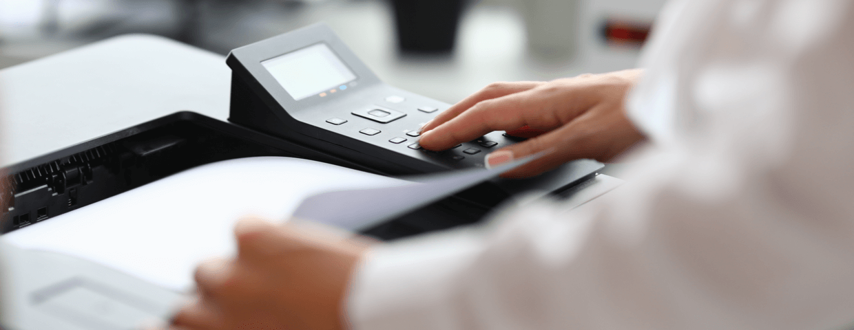 Closeup of business man with hands on top of desktop mfp, or multifunction printer in an office