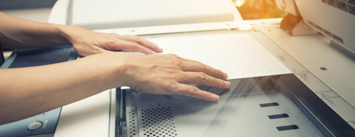 Closeup image of a womans hands putting a sheet of paper into a copying device